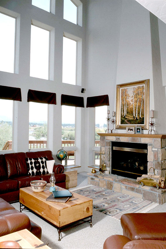 LIVING ROOM WITH VAULTED CEILING, STONE FIREPLACE SURROUND, AND WOOD MANTEL
