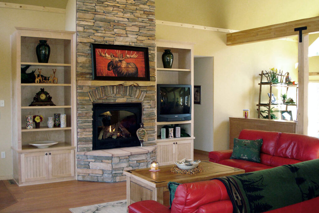 LIVING ROOM WITH STONE FIREPLACE, BUILT-IN BOOKCASES, AND WOOD FLOORING