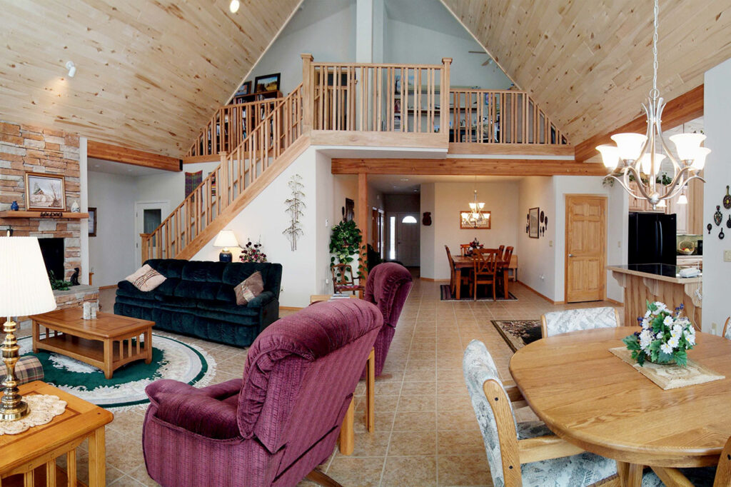 LIVING ROOM WITH STONE FIREPLACE, CUSTOM STAIR RAILING, AND CERAMIC TILE FLOORS