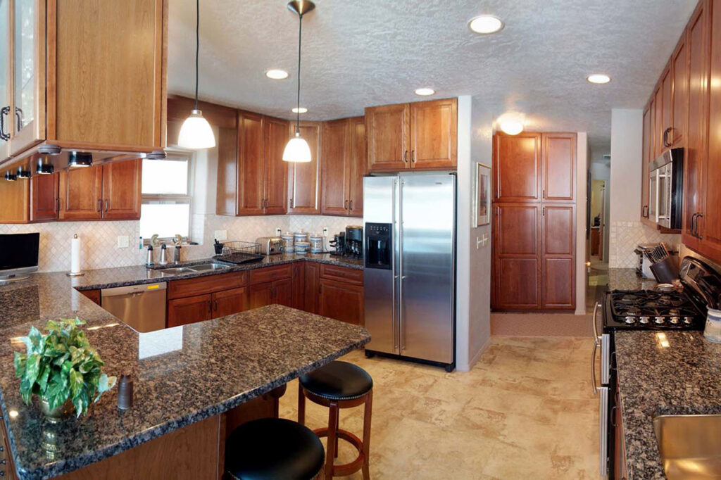 KITCHEN WITH SOLD GRANITE COUNTERTOPS, UNDER CABINET LIGHTING, AND DECORATIVE PENDANT LIGHTING