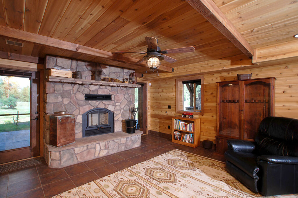 DEN WITH STONE FACED WOOD BURNING FIREPLACE, WOOD BEAMS, AND CERAMIC TILE FLOORS